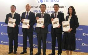 目論見書を手にフォトセッションに臨む同社役員。中央が谷口社長