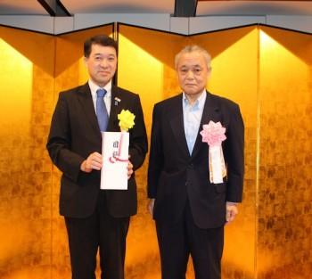 義援金の贈呈を受けた泉田裕彦知事(左)と佐藤孔一理事長(右)